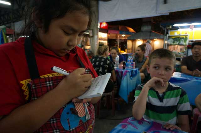 A Thai girl takes our order at an outdoor cafe, Chiang Mai. Thai street food