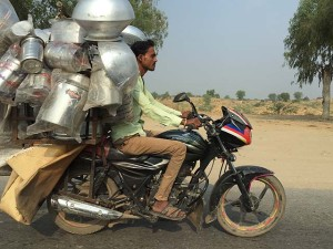 Indian man riding a fully laden motorbike