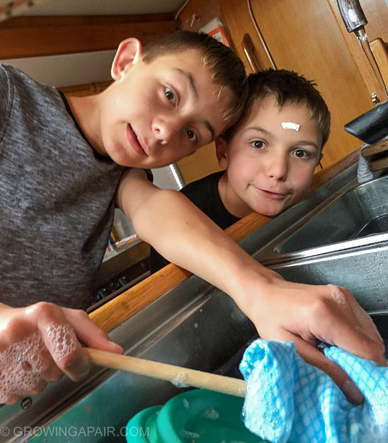 Kids washing the dishes on a bat