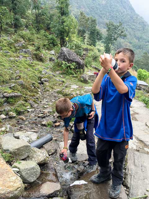 Water filter bottles being filled up from a stream in the Himalayas